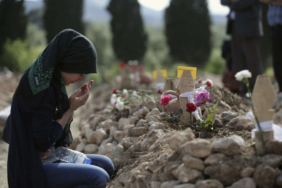 A woman prays at the grave of Ibrahim Duman, 26, a victim of the mine accident, in Soma, Turkey, Thursday, May 15, 2014. An explosion and fire at a coal mine in Soma, some 250 kilometers (155 miles) south of Istanbul, killed hundreds of workers, authorities said, in one of the worst mining disasters in Turkish history. (AP Photo/Emrah Gurel)