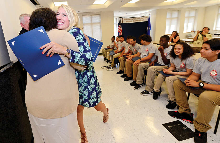 Dr. Marie Allen congratulates her staff member as students from Pathways Academy's Justice and Law Academy program celebrate their graduation for the program Wednesday, May 25, 2016 at the Norwalk Police Department Community Room Wednesday May 25, 2016. The community policing program is a collaboration between Pathway Academy and the Norwalk Police for at-risk students at the academy.