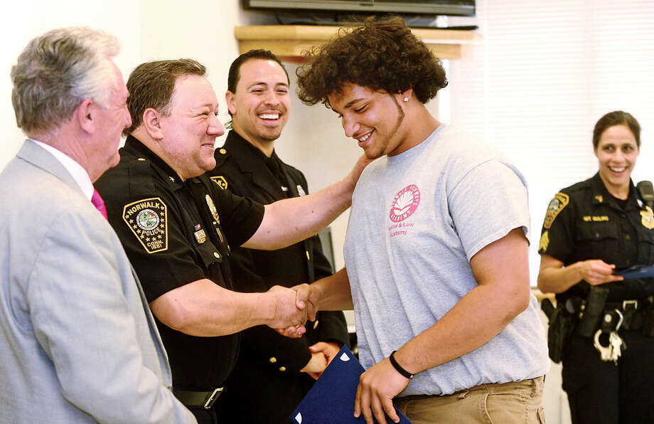 Students from Pathways Academy's Justice and Law Academy program including Blair Cantey celebrate their graduation for the program Wednesday, May 25, 2016 with congratulations from Norwalk Mayor, Harry Rillng, Deputy Police Chief, Ashley Gonzalez, School Resource Officer, Phil Taborda, and Seargent Sophia Golino, while at the Norwalk Police Department Community Room Wednesday May 25, 2016. The community policing program is a collaboration between Pathway Academy and the Norwalk Police for at-risk students at the academy.