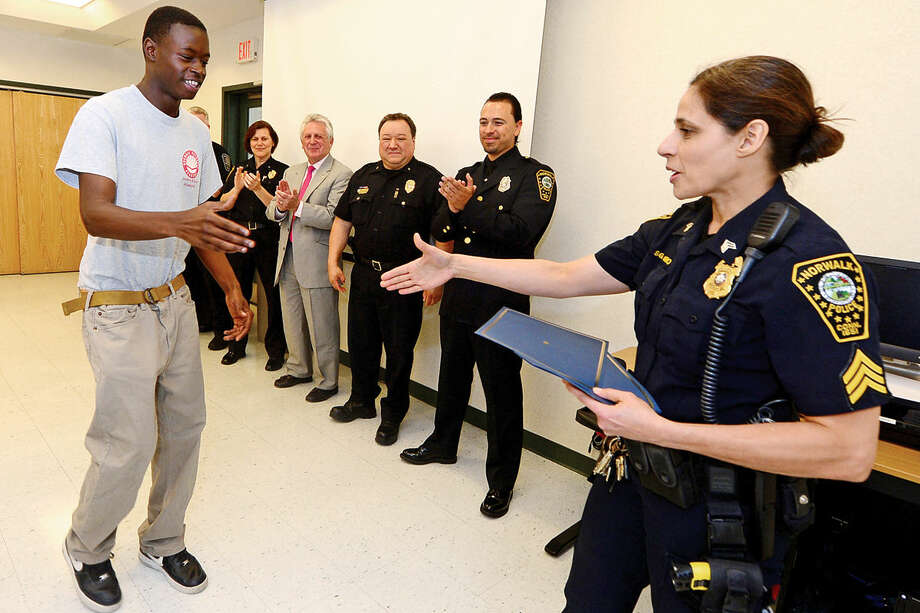 Seargent Sophia Golino congratulates students from Pathways Academy's Justice and Law Academy program including Tyrone Sherald as they celebrate their graduation for the program Wednesday, May 25, 2016 at the Norwalk Police Department Community Room Wednesday May 25, 2016. The community policing program is a collaboration between Pathway Academy and the Norwalk Police for at-risk students at the academy.