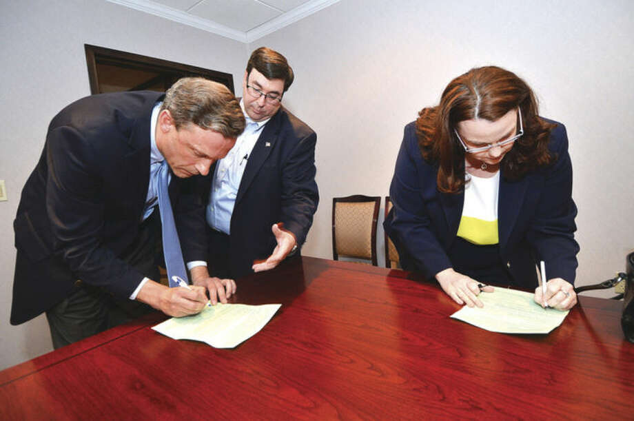 Hour Photo/ Alex von Kleydorff Art Scialabba former Norwalk Republican Town Committee Chairman looks over Fred Wilms and Emily D. Wilson as they sign paperwork after Wilson was nominated for State Rep District 142