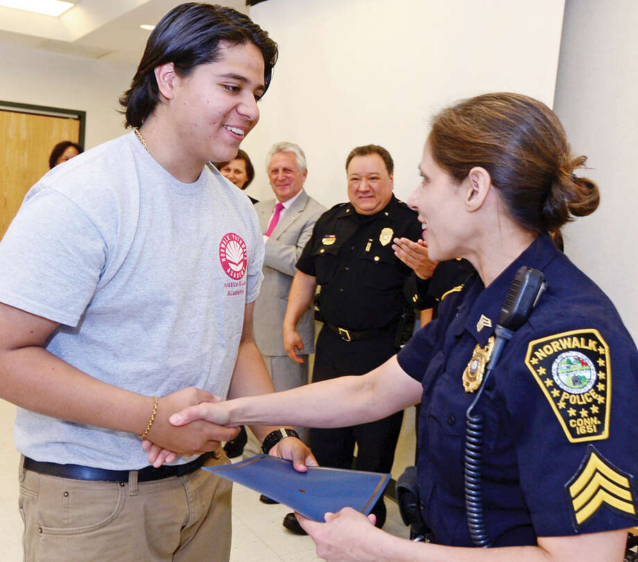 Norwalk Police Seargent Sophia Golina congratulates students from Pathways Academy's Justice and Law Academy program including Alejandro Villanova as they celebrate their graduation for the program Wednesday, May 25, 2016 at the Norwalk Police Department Community Room Wednesday May 25, 2016. The community policing program is a collaboration between Pathway Academy and the Norwalk Police for at-risk students at the academy.