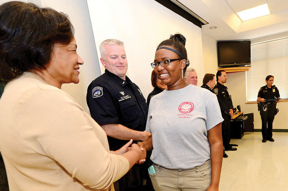 Pathwat Academy Principal Dr. Marie Allen and Lieutenant Terry Blake congratulate students from Pathways Academy's Justice and Law Academy program including Desiree Burton as they celebrate their graduation for the program Wednesday, May 25, 2016 at the Norwalk Police Department Community Room Wednesday May 25, 2016. The community policing program is a collaboration between Pathway Academy and the Norwalk Police for at-risk students at the academy.