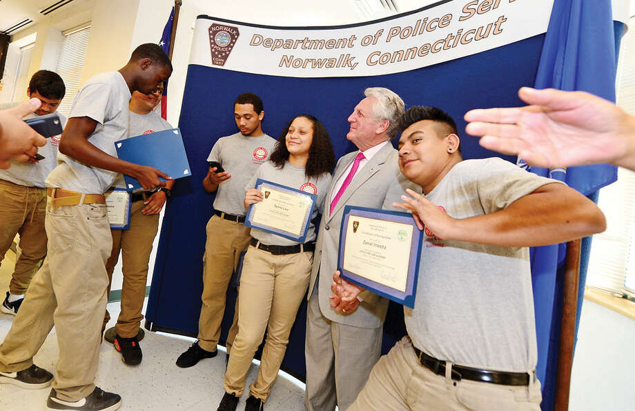 Students from Pathways Academy's Justice and Law Academy program pose for pictures with Norwalk Mayor Harry Rilling as they celebrate their graduation for the program Wednesday, May 25, 2016 at the Norwalk Police Department Community Room Wednesday May 25, 2016. The community policing program is a collaboration between Pathway Academy and the Norwalk Police for at-risk students at the academy.