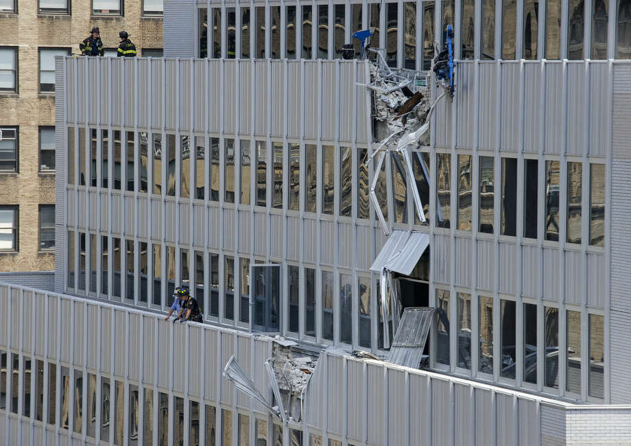 New York City firefighters stand near the damaged facade of 261 Madison Ave. after a piece of mechanical equipment being lifted by a crane broke free and fell about 28 stories to the sidewalk below, Sunday, May 31, 2015, in New York. Ten people including two construction workers were injured, but none of the injuries was considered life-threatening. (AP Photo/Craig Ruttle)
