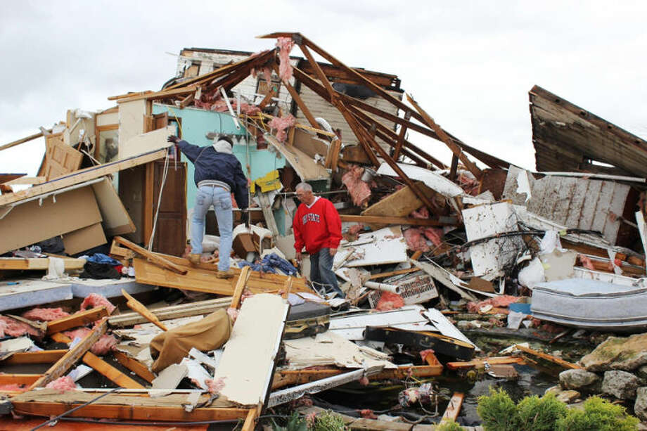 Roger Dobbins, right, and friend Keith Rose dig through the rubble left on Dobbins' farm Thursday, May 15, 2014, the day after a tornado destroyed it in Cedarville, Ohio. Flood watches remained in effect across much of eastern and northern Ohio Thursday as communities recovered from several days of heavy rain and storms, including a tornado that destroyed several buildings in western Ohio. (AP Photo/The Dayton Daily News, Darin Pope)