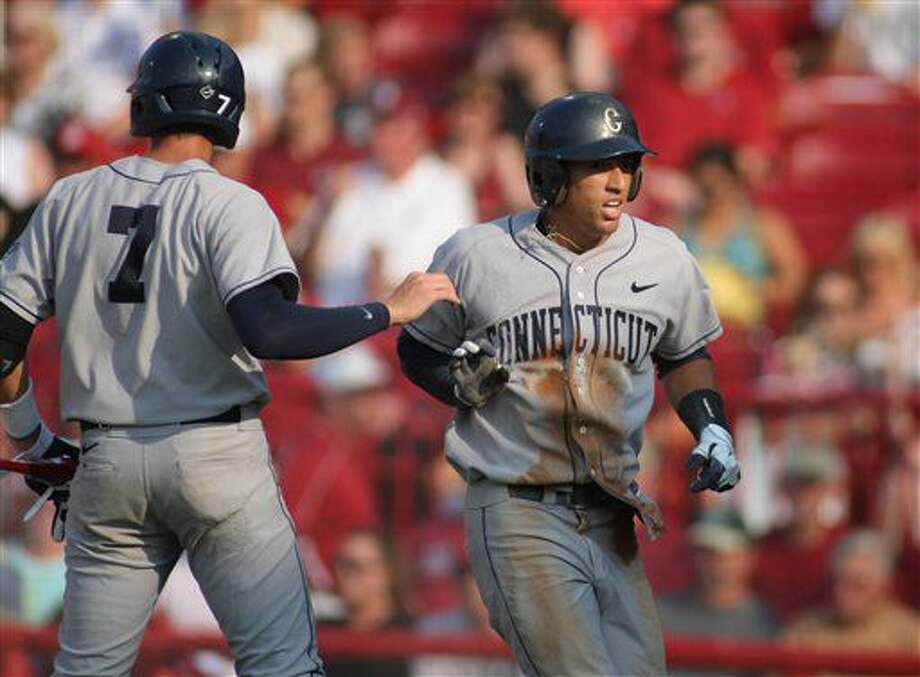 Connecticut's George Springer, right, is congratulated by teammate Nick Ahmed (7) after scoring a run in the first inning against South Carolina in a game at the NCAA Div. I college baseball super regionals at Carolina Stadium, Saturday, June 11, 2011, in Columbia, S.C.(AP Photo/Willis Glassgow)