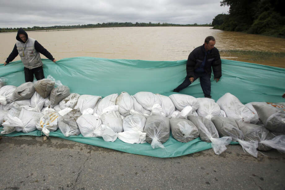 Residents lay sand bags along a flooded road in the village of Hrtkovci, 60 kilometers west of Belgrade, Serbia, Saturday, May 18, 2014. Record flooding in the Balkans leaves at least 20 people dead in Serbia and Bosnia and is forcing tens of thousands to flee their homes. Meteorologists say the flooding is the worst since records began 120 years ago. (AP Photo/Darko Vojinovic)