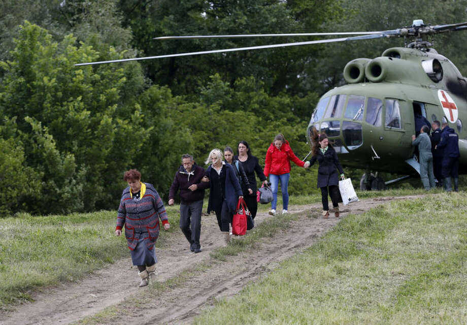Evacuated people leave a military helicopter near Obrenovac, some 30 kilometers (18 miles) southwest of Belgrade Serbia, Saturday, May 17, 2014. Record flooding in the Balkans leaves at least 20 people dead in Serbia and Bosnia and is forcing tens of thousands to flee their homes. Meteorologists say the flooding is the worst since records began 120 years ago. (AP Photo/Darko Vojinovic)