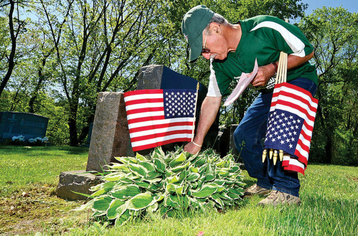 Hour photo / Erik Trautmann Guy Taccone places flags at St. John's Cemetary in Norwalk as King Industiries takes over from Northrop Grumman in sponsoring the placement of new American flags on the grave sites of veterans at local cemeteries