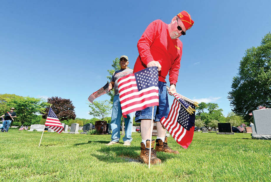 Hour photo / Erik Trautmann Peter haven places flags at St. John's Cemetary in Norwalk as King Industiries takes over from Northrop Grumman in sponsoring the placement of new American flags on the grave sites of veterans.