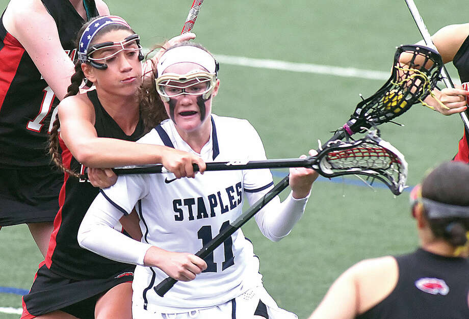 Staples High School's Colleen Bannon, front, finds herself getting checked from behind while making a rush toward goal during the second half of Monday's CIAC Class L girls lacrosse state tournament game in Westport. The host Wreckers topped the Mustangs 11-8. (Hour photo/John Nash)