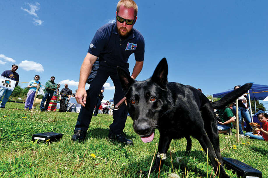 Hour photo / Erik Trautmann Norwalk Police Officer with the K-9 unit Dave Peterson and his dog, Rainor, perform a demonstration during The Hour Parade of Pets Pet Expo Saturday at Taylor FarmPark.