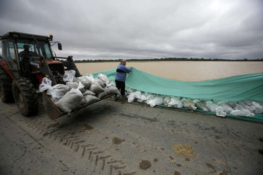 Residents lay sand bags along a flooded road in the village of Hrtkovci, 60 kilometers west of Belgrade, Serbia, Saturday, May 17, 2014. Record flooding in the Balkans leaves at least 20 people dead in Serbia and Bosnia and is forcing tens of thousands to flee their homes. Meteorologists say the flooding is the worst since records began 120 years ago. (AP Photo/Darko Vojinovic)