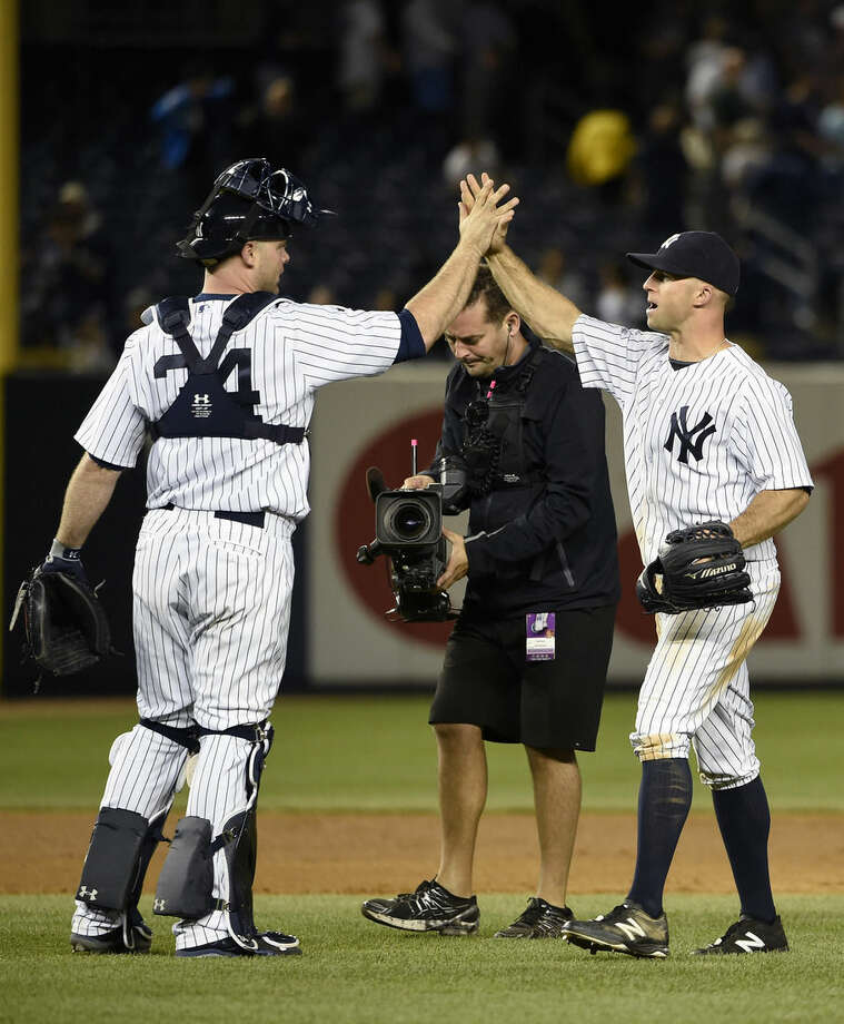 New York Yankees catcher Brian McCann (34) high-fives with left fielder Brett Gardner after they defeated the Los Angeles Angels 8-2 in a baseball game on Saturday, June 6, 2015, in New York. (AP Photo/Kathy Kmonicek)