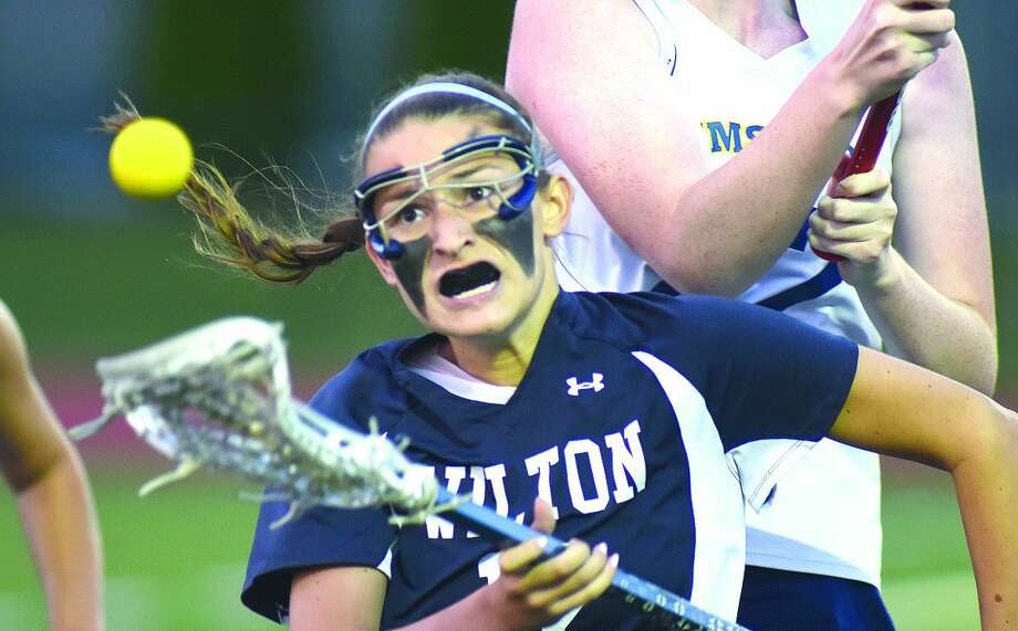 Hour photo/John Nash - Eliza Chapey of Wilton keeps her eye on the ball while in a crowd of Simsbury players during Thursday's CIAC Class L girls lacrosse state tournament semifinal in Southington. Wilton coasted to a 16-4 win.