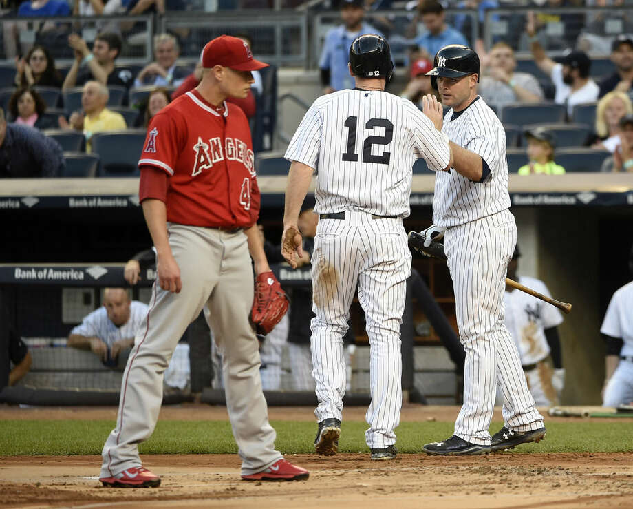 Los Angeles Angels starting pitcher Garrett Richards reacts at home plate as New York Yankees' Chase Headley (12) is greeted by Brian McCann after Headley scored on a wild pitch in the first inning of a baseball game at Yankee Stadium on Saturday, June 6, 2015, in New York. (AP Photo/Kathy Kmonicek)