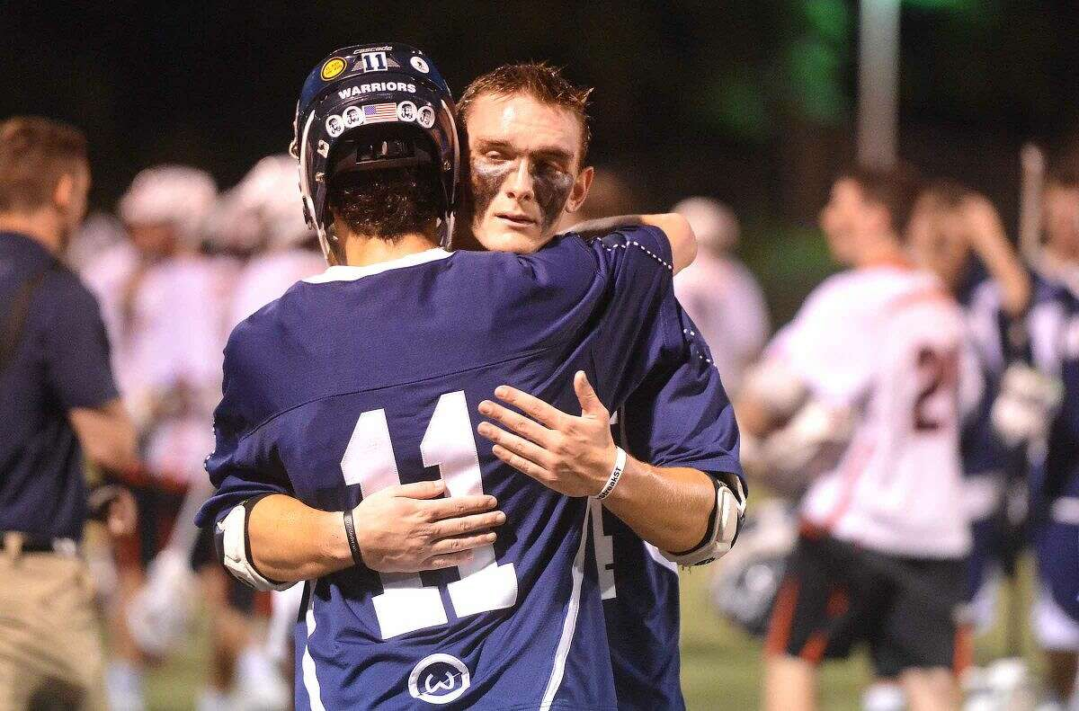 Hour Photo/Alex von Kleydorff Wiltons Michael Brown gives a hug to John Dexter at The Warriors come off the fields after losing to New Cannan Lacrosse