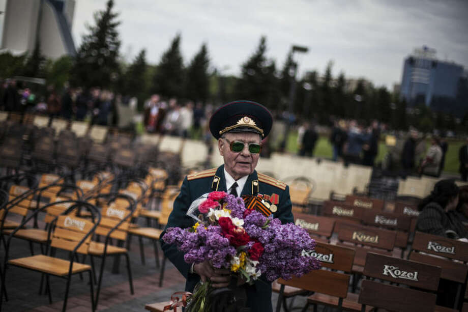 FILE - In this May 9, 2014, file photo, a veteran from the Red Army holds a bouquet of flowers while attending the commemoration of Victory Day in Donetsk, Ukraine. The crisis in Ukraine is giving Russia an opening to drive a wedge between the United States and Europe just as Western powers try to repair a struggling trade deal and decide how to bolster a cash-strapped NATO. (AP Photo/Manu Brabo, File)