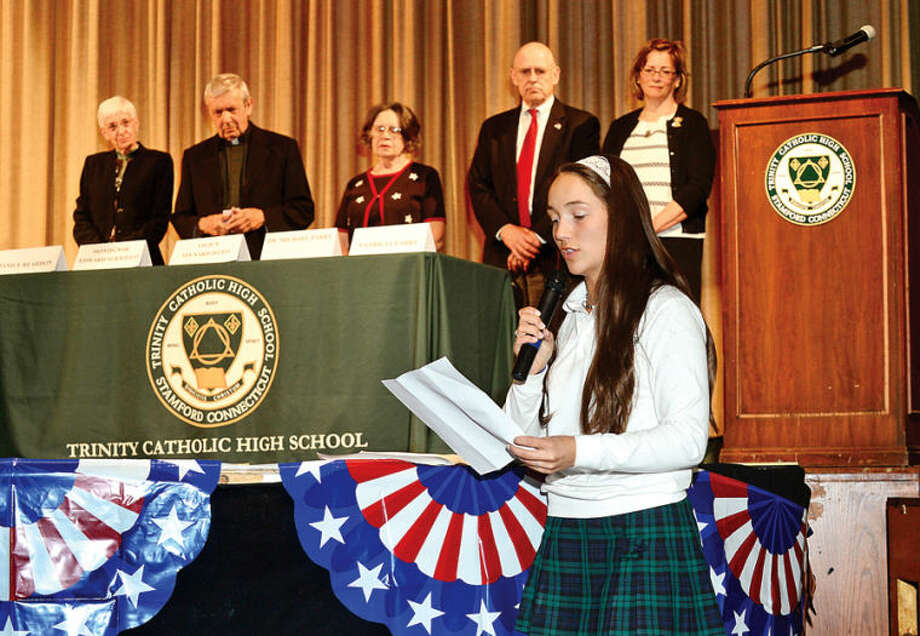 Hour photo / Erik Trautmann Trinity Catholic High School student Linsey McMahon performs a reading as the school hosts Memorial Day assembly Wednesday to honor veterans Thomas Morris, Robert Dwyer, Norman Spenard and Brian Bill, four graduates who gave their lives for their country.
