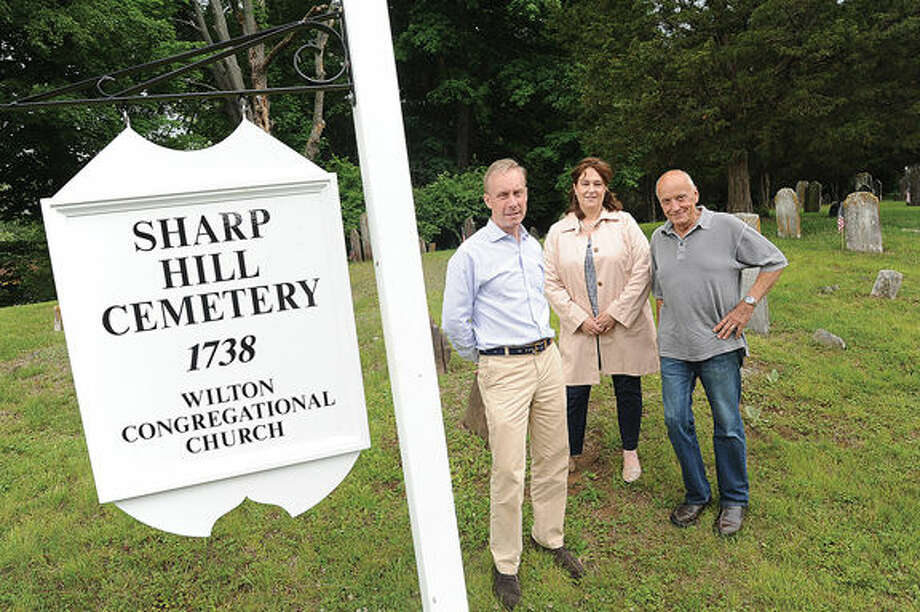 Bill Follett, chairman of the buildings and grounds committee, Pamela Brown, executive administrator of the Wilton Congregational Church and Hillside Cemetery, and Ian Tesar, with the buildings and grounds committee as well as the builder of the new sign at the Sharp Hill Cemetery.