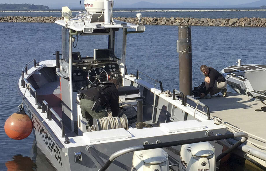 A Vermont State Trooper prepares to head out on Lake Champlain, Thursday, June 11, 2015, in Burlington, Vt., as part of an effort to look for two escaped New York prison inmates who have been on the run for almost a week. (New England Cable News/Jack Thurston via AP)