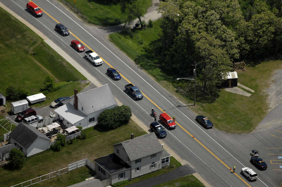 A road is blocked by authorities in Cadyville, N.Y., as police search for David Sweat, 34, and Richard Matt, two escaped inmates on Thursday, June 11, 2015. Schools were closed, and residents received automated calls warning them to lock their doors, close their windows and leave outside lights on. (AP Photo/Tim Roske)