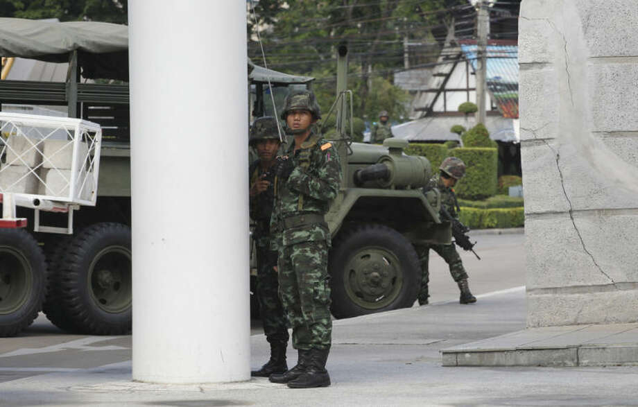 Thai soldiers take position behind a military vehicle in the compound of the Army Club after the military staged the coup Thursday, May 22, 2014 in Bangkok, Thailand. Thailand's army chief announced a military takeover of the government Thursday, saying the coup was necessary to restore stability and order after six months of political deadlock and turmoil. (AP Photo/Apichart Weerawong)