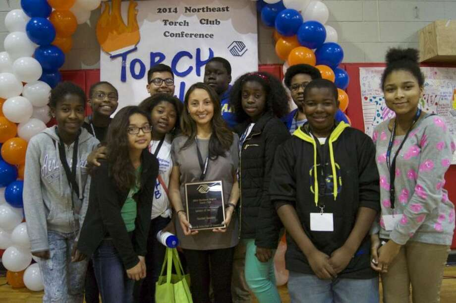 Torch Club Advisor, Maribel Sandalo, winning the Northeast Torch Club Advisor of the Year Award.  She is shown surrounded by her Stamford Torch Club members.