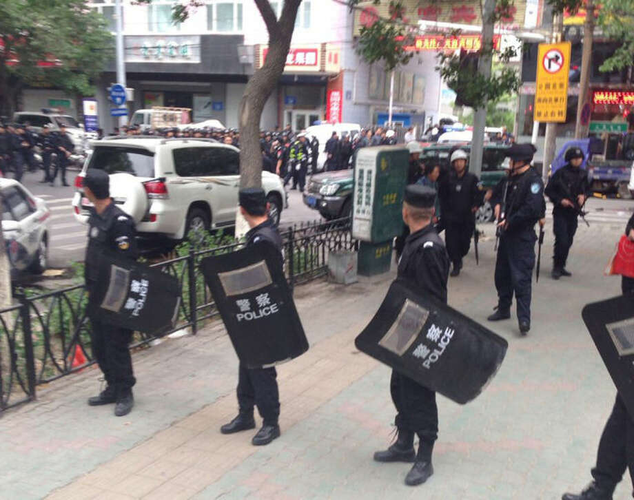In this photo released by China's Xinhua News Agency, police officers stand guard near a blast site which has been cordoned off, in downtown Urumqi, capital of northwest China's Xinjiang Uygur Autonomous Region, Thursday, May 22, 2014. Attackers crashed a pair of vehicles and tossed explosives in an attack Thursday near an open air market in the capital of China's volatile northwestern region of Xinjiang, leaving an unknown number of people dead and injured, state media reported. (AP Photo/Cao Zhiheng)