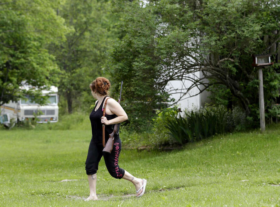 Jennifer Hilchey-Reyell watches the tree line as she carries a .22 rifle walking from her mother's house to her own house near Dannemora, N.Y., Thursday, June 11, 2015. Hilchey-Reyell has been keeping a gun close at hand since the escape of two prisoners from the maximum-security Clinton Correctional Facility near her home. (AP Photo/Seth Wenig)