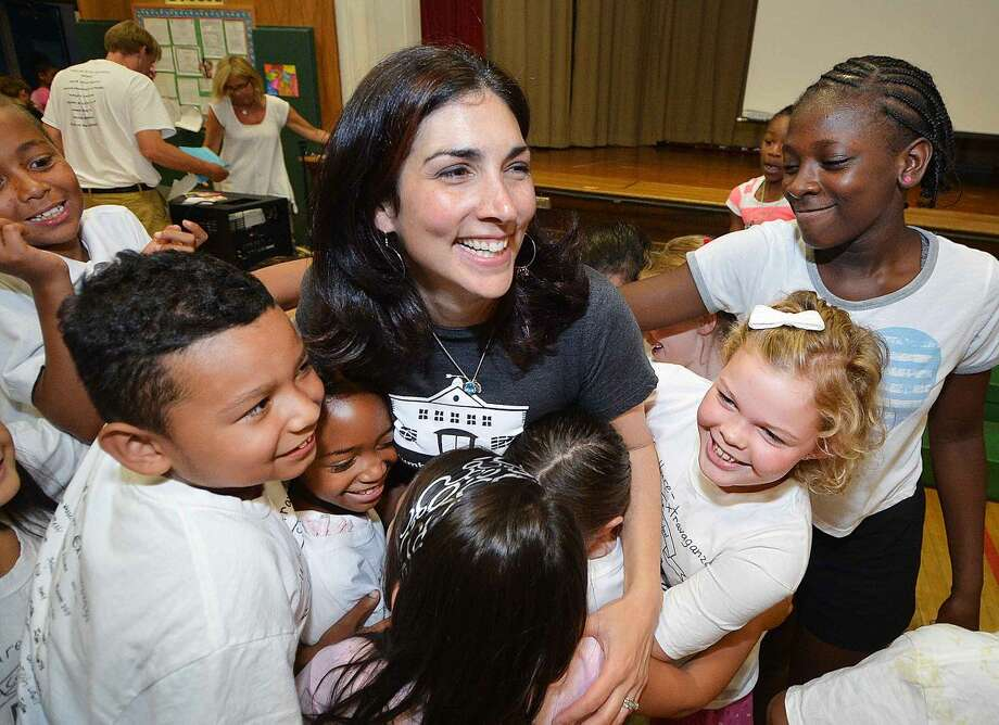 Hour Photo/Alex von Kleydorff Columbus Magnet School Principal Emily Lopez gets hugs from the students during an all school program to honor her and say farwell as she is leaving June 30th to work with the Lily Sarah Grace Fund