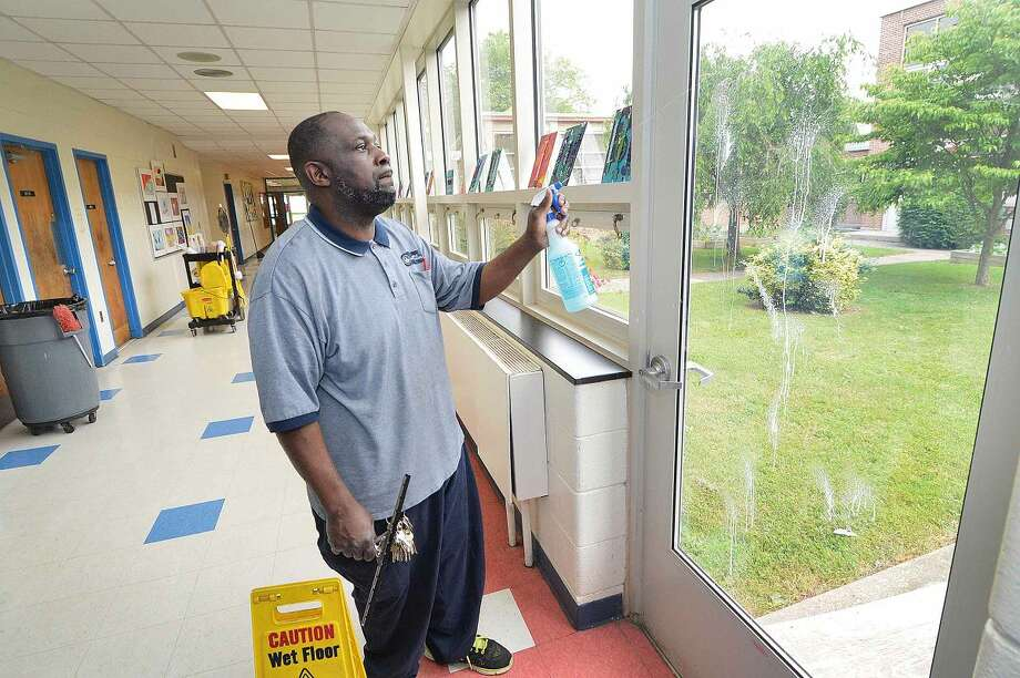 Hour Photo/Alex von Kleydorff Nathan Hale School Head Custodian and Local 1042 Union President Stanley Shuler keeps the windows clean during his rounds at Nathan Hale