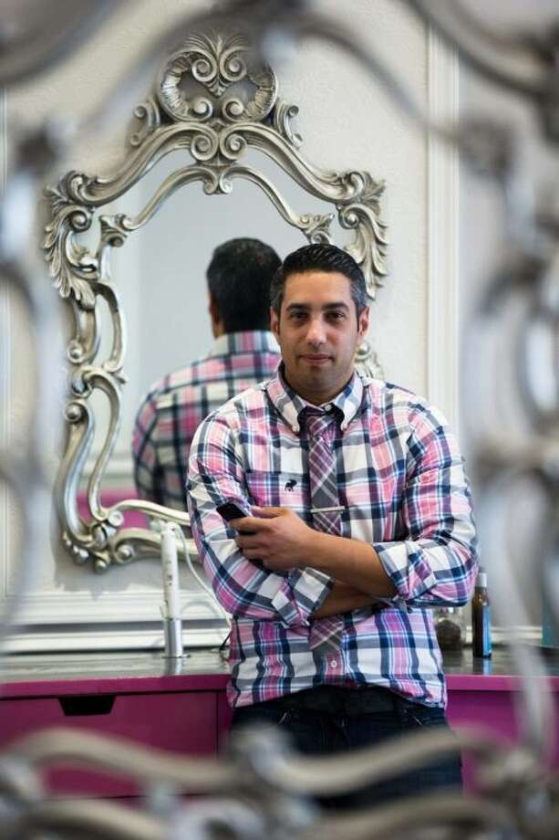 In this May 19, 2014 photo, Avi Shenkar, owner of Blo/Out Blow Dry Bars, poses for a photograph with his iPhone, in Philadelphia. Smartphones have become vital for on-the-go entrepreneurs such as Shenkar who runs his four hair salons from the palm of his hand. (AP Photo/Matt Rourke)