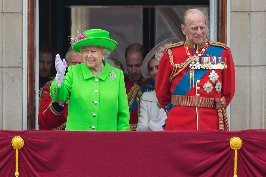 The queen and her husband, Prince Philip, who turned 95 Friday, wave from the balcony of Buckingham Palace. Photo: JUSTIN TALLIS, AFP/Getty Images
