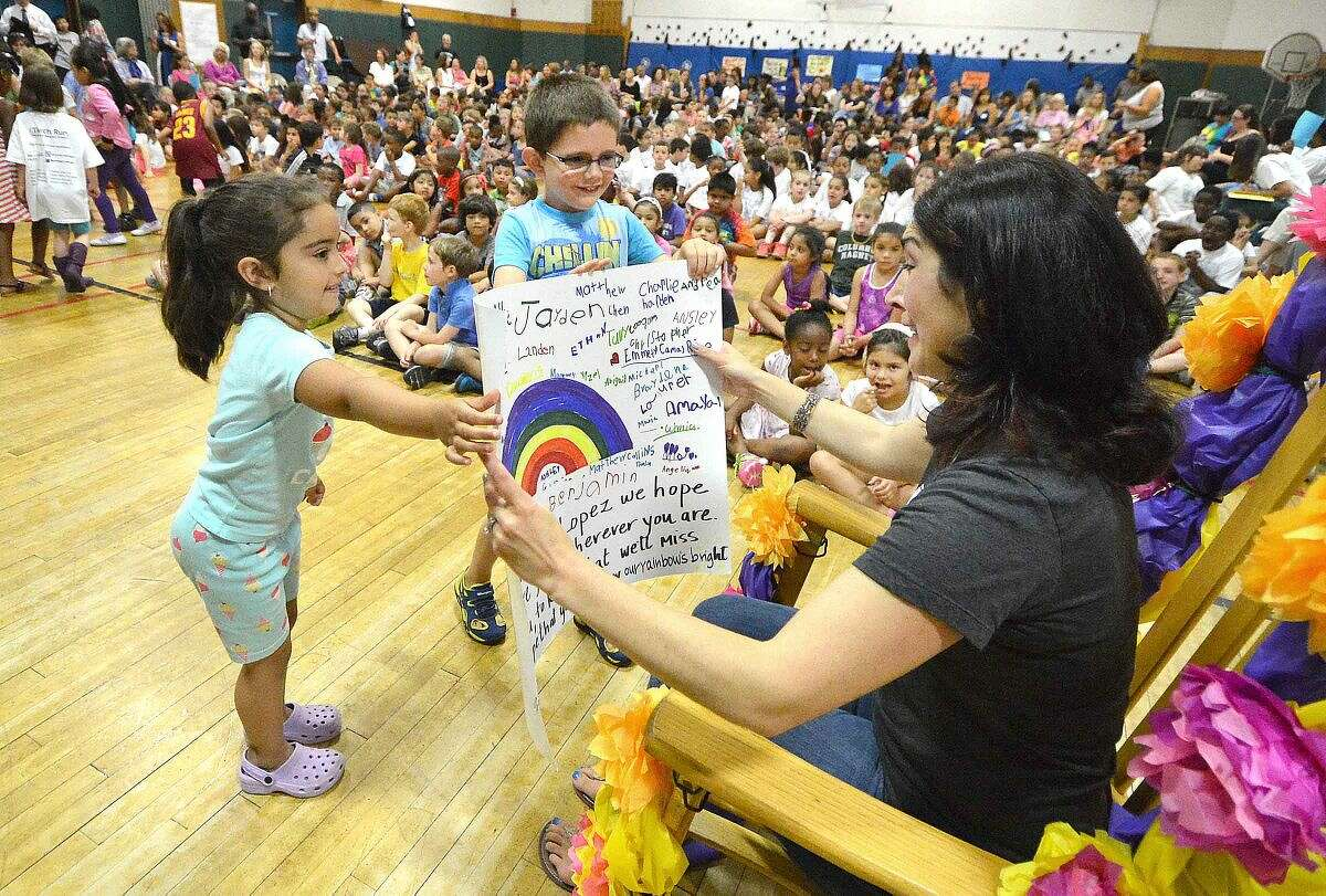 Hour Photo/Alex von Kleydorff Columbus Magnet School Principal Emily Lopez gets a card from the students in K-162, K 1-192 after they sang Our School's a Rainbow during an all school program to say farwell as she is leaving June 30th to work with the Lily Sarah Grace Fund