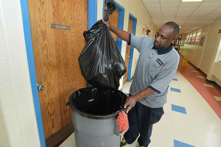 Hour Photo/Alex von Kleydorff Nathan Hale School Head Custodian and Local 1042 Union President Stanley Shuler empties some of the trash bags at Nathan Hale on Thursday