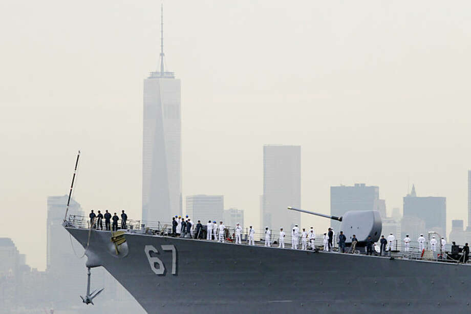 Sailors line the bow of the destroyer USS Cole as it glides past One World Trade Center and the lower Manhattan skyline, Wednesday, May 21, 2014 in New York. A slimmed down version of Fleet Week, the city's annual celebration of the sea and sailors, sails into town one year after federal budget cuts decimated the event. (AP Photo/Mark Lennihan)