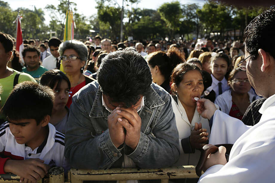 Faithful partake in the Catholic sacrament of communion as they participate in the Corpus Christi mass in Caacupe, Paraguay, Sunday, June 7, 2015. Catholics take part in a procession through the streets of a neighborhood near their parish following mass and pray and sing celebrating the tradition and belief in the body and blood of Jesus Christ. (AP Photo/Jorge Saenz)
