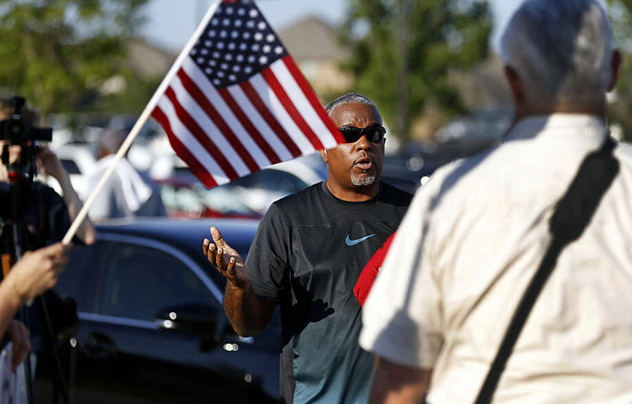 Jerry Johnson, left, of McKinney, debates a supporter of the police during a protest Monday, June 8, 2015, in response to an incident at a community pool involving McKinney police officers in McKinney, Texas. (AP Photo/Ron Jenkins)