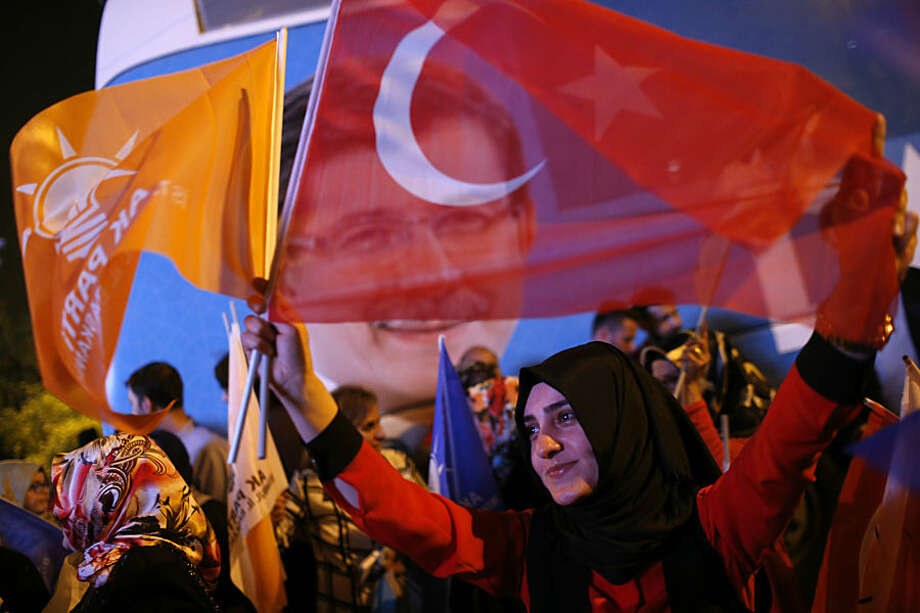 Supporters of Turkey's ruling Justice and Development Party celebrate over the election results in Istanbul,Turkey, late Sunday, June 7, 2015. With 99.9 percent of the vote counted, President Recep Tayyip Erdogan's AKP had the support of around 41 percent of voters, state-run TRT television said. (AP Photo/Emrah Gurel)