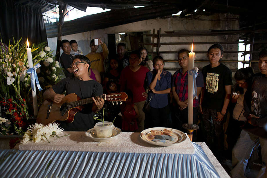 Family and close friends look on as a friend of Antonio Vivar Diaz, 28, sings at his wake in Tlapa, Guerrero State, Mexico, Monday, June 8, 2015. Vivar was killed Sunday night in aconfrontation in which policerescuedfellow officersheld by a group of dissident teachers, who had captured them to exchange for teachers arrested earlier by police. (AP Photo/Rebecca Blackwell)