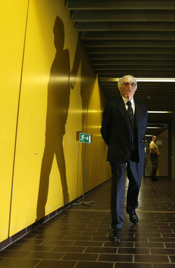 """Formula One boss Bernie Ecclestone arrives for another day of his trial at the regional court in Munich, Germany, Wednesday May 21, 2014. Ecclestone is charged with bribery and incitement to breach of trust """"in an especially grave case"""" over a US dollar 44 million payment to a German banker, that prosecutors allege was meant to facilitate the sale of the Formula One Group to a buyer of Ecclestone's liking. (AP Photo/Michaela Rehle, Pool)"""