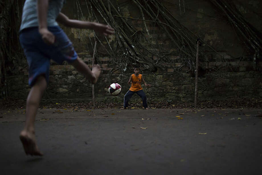 Children play soccer in the ruins of Paricatuba, near Manaus, Brazil, Wednesday, May 21, 2014. Manaus is one of the host cities for the 2014 World Cup in Brazil. (AP Photo/Felipe Dana)