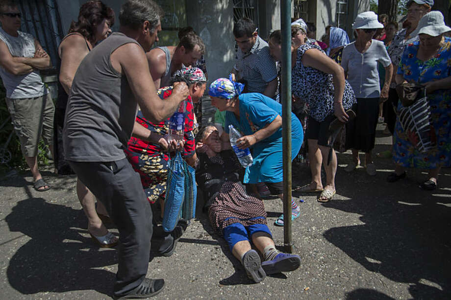 Local citizens help a lady from fainting while attending a rally in protest against a shelling from Ukrainian government forces in the village of Semyonovka, near the major highway which links Kharkiv, outside Slovyansk, Ukraine, Thursday, May 22, 2014. Several trains carrying weapons and planeloads of troops have left regions near Ukraine as part of a massive military pullout, the Russian Defense Ministry said Thursday, even as fighting raged between pro-Russian insurgents and government forces in eastern Ukraine. (AP Photo/Alexander Zemlianichenko)