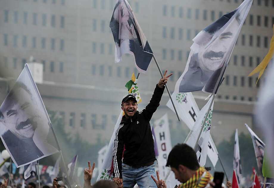 A supporter of the pro-Kurdish Peoples' Democratic Party, (HDP) flashes the V-sign as others wave flags of imprisoned Kurdish rebel leader Abdullah Ocalan, during a rally in Istanbul, Turkey, Monday, June 8, 2015, a day after the elections. The biggest change from Turkey's previous parliament is the ascendancy of the People's Democratic Party, a socially liberal force rooted in the Kurdish nationalism of Turkey's southeast. It attracted more than 12 percent of votes, breaching the minimum threshold of 10 percent. Turkey's President Recep Tayyip Erdogan's long-ruling Justice and Development Party(AKP), has suffered surprisingly strong losses in parliament that will force it to seek a coalition partner for the next government. (AP Photo/Lefteris Pitarakis)