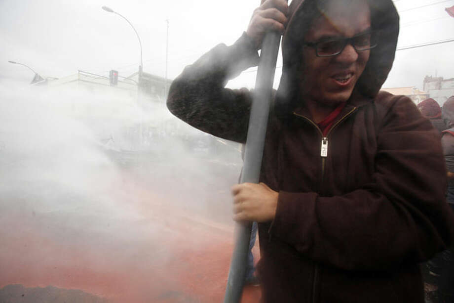 A protestor braces as police fire a water cannon at demonstrators during clashes in Valparaiso, Chile, Wednesday, May 21, 2014. Protesters believe the education reforms proposed Monday by President Michelle Bachelet are not enough. Bachelet proposed an end to state subsidies to for-profit schools. Still to come is a proposal that would make university education free in Chile. (AP Photo/Luis Hidalgo)
