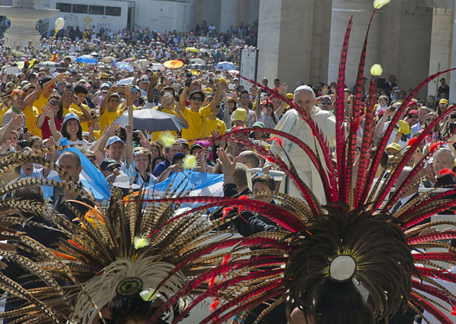 Pope Francis greets a group of representatives from various indigenous people as he arrives for his weekly general audience in St. Peter's Square at the Vatican, Wednesday, May 21, 2014. (AP Photo/Alessandra Tarantino)