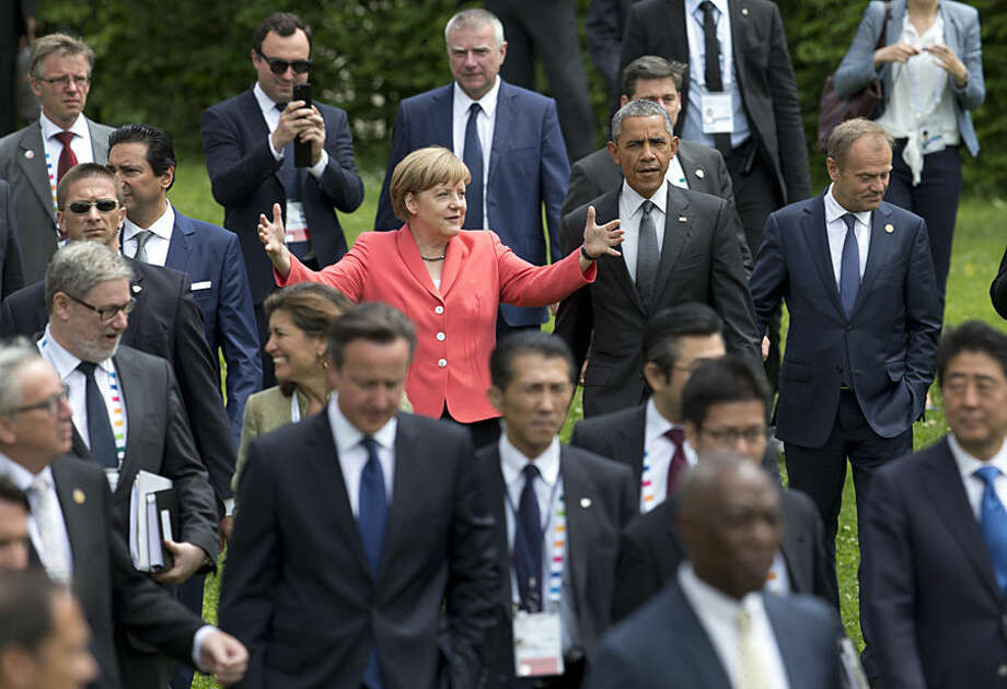 US President Barack Obama, center right, and German Chancellor Angela Merkel, center left, walk to a group photo of G-7 leaders and Outreach guests at the G-7 summit in Schloss Elmau hotel near Garmisch-Partenkirchen, southern Germany, Monday, June 8, 2015. To the right of Obama is European Council President Donald Tusk. (AP Photo/Carolyn Kaster)