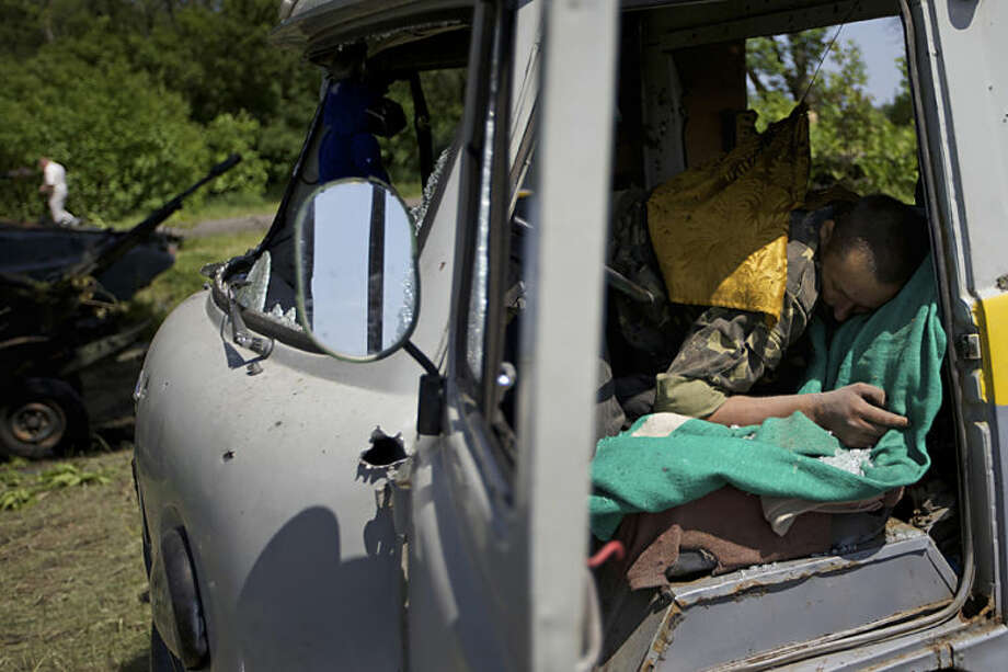 A body seen in a destroyed car near the village of Blahodatne, eastern Ukraine, on Thursday, May 22, 2014. At least 11 Ukrainian troops were killed and about 30 others were wounded when Pro-Russians attacked a military checkpoint, the deadliest raid in the weeks of fighting in eastern Ukraine. Three charred Ukrainian armored infantry vehicles, their turrets blown away by powerful explosions, and several burned vehicles stood at the site of the combat. (AP Photo/Ivan Sekretarev)